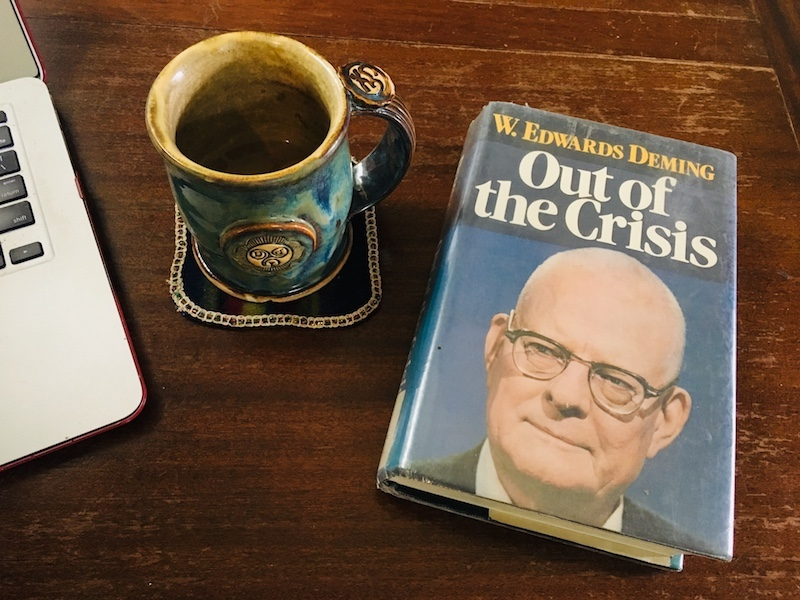Deming's book Out of the Crisis on a table with a cup of coffee and a laptop. The table needs some furniture polish.