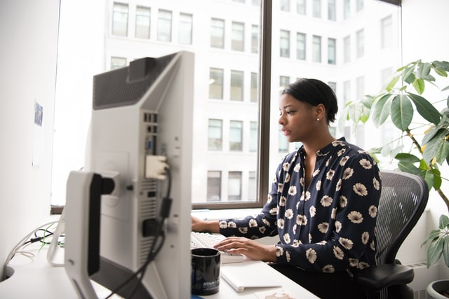 woman typing at computer-meetings that could have been an email